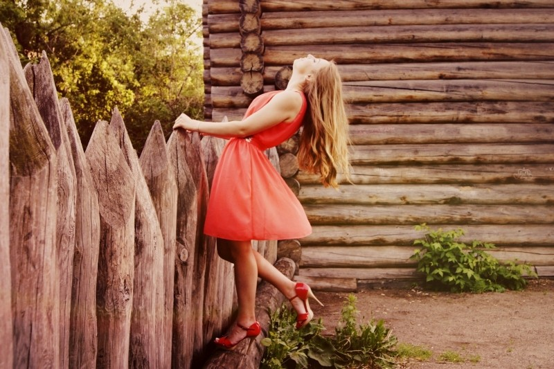 woman-in-orange-dress-leaning-against-wooden-fence