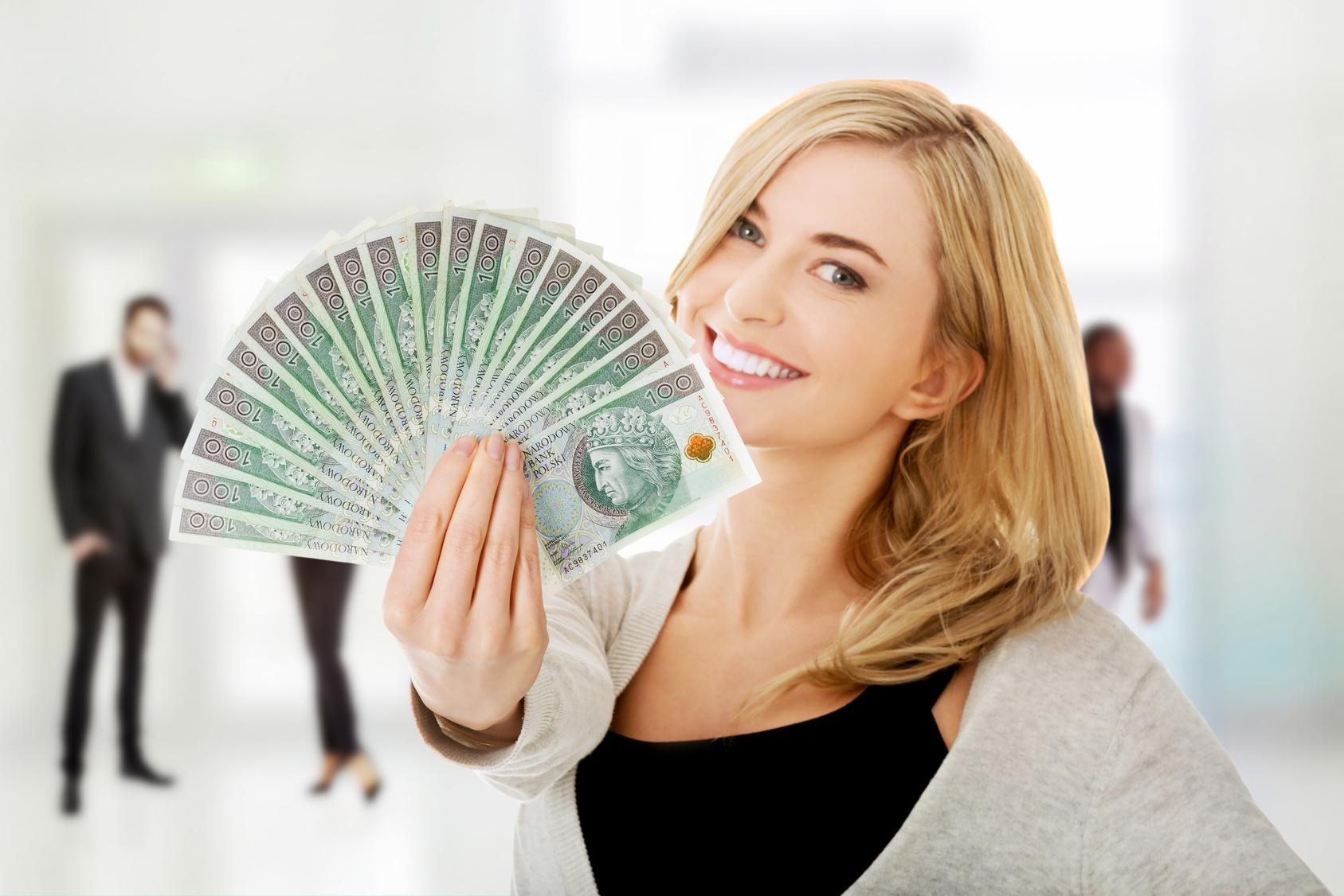 Happy woman holding polish banknotes.